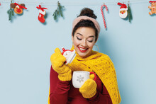 Young Woman 20s Years Old Wears Yellow Mittens Scarf Sweater Hold Open Smell Snowman Cup Coffee Tea Isolated On Plain Pastel Light Blue Background Studio Portrait. Happy New Year 2022 Holiday Concept.