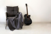 Home Interior: Close-up Of Comfortable Grey Armchair With Grey Blanket And Black Guitar Next To It In Room