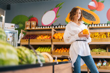 Low-angle View Of Attractive Young Woman Holding In Hands Big Fresh Pomegranate Posing Standing At Fruit And Vegetables Section Of Grocery Store, Looking At Camera, Selective Focus, Blurred Background