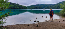 A Girl Stands Near The Shore And Looks At The Ducks. Lake And Nature In The Plitvice Lakes National Park. Passenger Ferry. Trees And Blue Water In Lake. Green Hills. Overcast Weather. Croatia. Europe