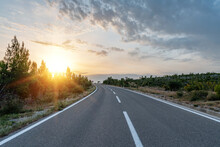Scenic Road. The Road Is Surrounded By A Magnificent Natural Landscape In The Rays Of Sunset Or Dawn.