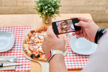 Close-up Of A Man Taking Pictures Of A Pizza With His Phone
