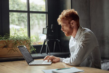 Young Red Head Man Using Laptop At Wooden Desk