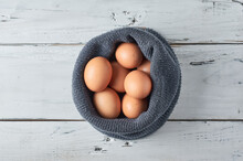 Eggs Inside A Gray Wool Cap On A Rustic White Table.