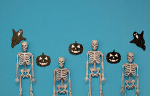 Happy Halloween Concept. Halloween Skeleton Background On Blue Background With Pumpkins And Ghosts. The Concept Of Decoration. Flat Position, Top View. Space For Text