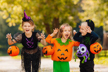 Happy Halloween. Three Running Kids With A Basket For Sweets