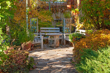 Beautiful Gazebo With White Benches And A Table In The Garden With Decorative Plants With Colorful Yellow-orange Red Autumn Leaves