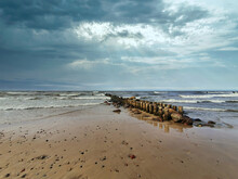 Dramatic Cloudy Sky Over Empty Sandy Beach On The Baltic Sea Coast With Stormy Waves Rolling On Old Wooden Breakwater At Dusk Or Dawn. With No People Scenic Seaside Landscape.