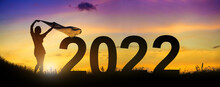 Silhouette Enjoying Women Flapping A Thin Fabric On The Hill While Celebrating 2022 Years In The Twilight Background.