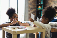 Two African American Girl Do Activities Together At Home By Drawing.