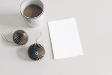 Winter Holiday Stationery Mockup. Brown Paper Christmas Ornaments And Cup Of Coffee Isolated On White Table Background. Blank Greeting Card, Invitation. Flat Lay, Top View. No People. Paper Balls.