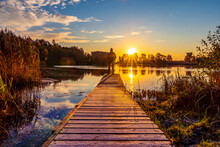 Silhouette Of Man Standing On The Lake Wooden Bridge Facing To The Sunrise