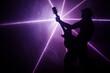 Mężczyzna z gitarą na tle światła laserowego