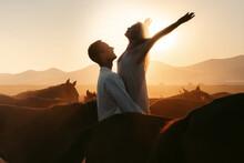 Man Raising Woman Among Horses In Sundown