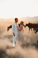 Soulmates Standing In Dusty Field With Horses In Summertime