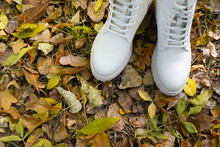A Pair Of White Fashion Leather Boots In Natural Outdoor Setting Autumn Leaves Background