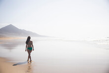 Back View Of Woman Strolling On The Beach At Low Tide, Fuerteventura, Spain