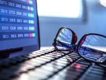 Stock Market Data Reflecting In Eyeglasses Lying On Laptop Keyboard