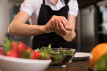 Close-up Of Woman Cooking In Kitchen Preparing A Salad