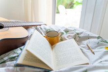 Guitar, Coffee Cup, Pencil And Open Book On Bed