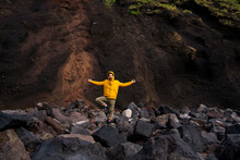 Man Standing Amidst Volcanic Rocks In Yoga Pose, Sao Miguel Island, Azores, Portugal