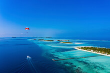 Maledives, South Male Atoll, Paraglider Flying Along An Atoll, Aerial View