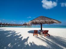 Maldives, Empty Deck Chairs Under Straw Umbrella On Sandy Coastal Beach In Summer