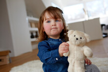 Portrait Of Toddler Girl With Teddy Bear Sitting On The Floor At Home