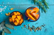 Bowls Of RedÔøΩkuriÔøΩsquashÔøΩ(CucurbitaÔøΩmaxima) Slices, Rosemary, Sage, Salt And Pepper Lying On Blue Cutting Board