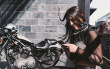 Young Woman Using Smarphone, Next To Her Motor Bike