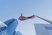USA, New York, New York City, Directly Below View Of Clear Sky Over American Flag And Manhattan Skyscrapers