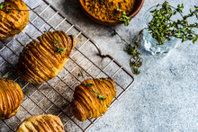 Bowl Of Hasselback Potatoes With Fresh Thyme On A  Metal Cooling Rack