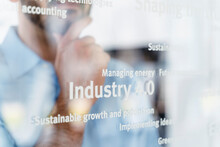 Businessman With Hand On Chin In Front Of Glass Pane With Words, Industry 4.0