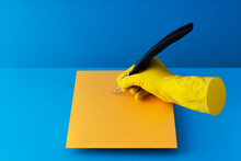 Quill Pen Held In Hand And Writing On Orange Paper Over Blue Background