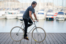 Mature Man Riding Bicycle On Boardwalk, Alicante, Spain