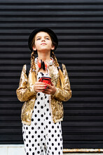 Portrait Of Girl With Smartphone Wearing Hat, Golden Sequin Jacket And Polka Dot Jumpsuit Thinking