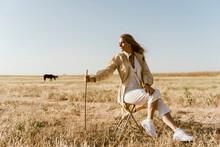 Female Traveller Sitting On Stool, Meadow