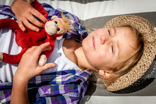 Little Girl With Cuddly Toy Lying In Sunshine