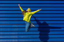 Teenage Girl Jumping In The Air In Front Of Blue Background Listening Music With Headphones