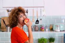 Portrait Of Woman Eating An Apple In Office Kitchen