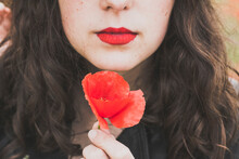 Crop View Of Young Woman With Red Lips Holding Poppy