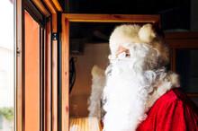 Man Wearing Santa Claus Costume Looking Through Window At Home