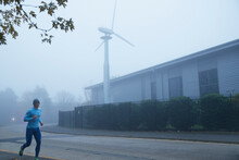 Man Jogging Along Foggy Street With Wind Turbine In Background