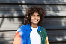 Smiling Man Wearing Headphones Listening Music While Standing Against Black Wall