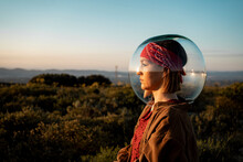 Woman With A Fish Bowl On Her Head In The Countryside