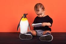 Baby Girl Ignoring Toy While Using Mobile Phone Sitting Against Orange Background