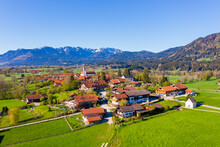 Germany, Bavaria, Wackersberg, Drone View Of Rural Town In Spring With Brauneck And Benediktenwand Mountains In Background