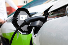 Close-up Of Electric Plug In Hybrid Car At Station With Man In Background