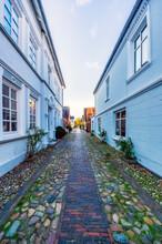 Cobblestoned Narrow Alley Between Blue Buildings