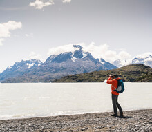 Man Looking At Grey Glacier View Through Binocular In Torres Del Paine National Park, Patagonia, Chile, South America